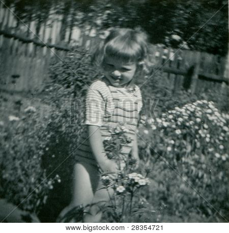 Vintage photo of young girl playing outdoor (fifties)