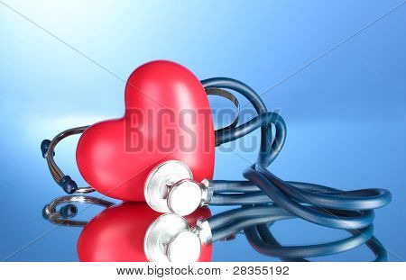 Medical stethoscope and heart  on blue background