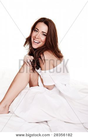 Laughing Happy Young Woman sitting on a bed swathed in white bedclothes, studio on white