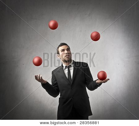 Businessman juggling with some balls