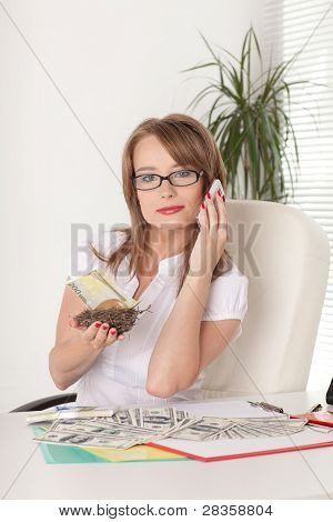 Businesswoman Holds  Nest With A Golden Egg And Money.