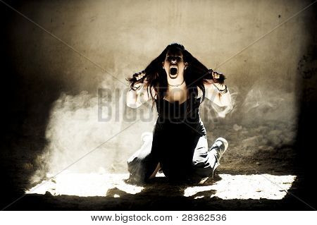 Screaming young gothic woman in old house