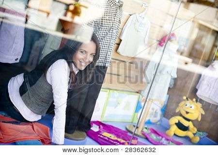 Young beautiful shop assistant working at the shop window