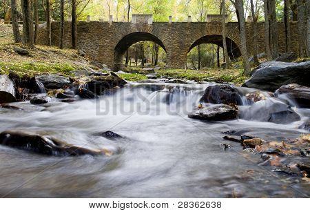 Beautiful old stone bridge over stream water, long exposure