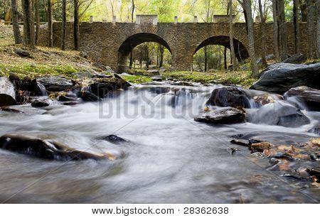 Beautiful old stone bridge over stream water, long exposure