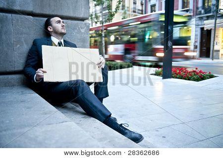 Empresario desempleado con un cartel de cartón en blanco con fondo borroso