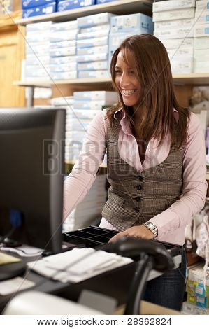 Beautiful young shop assistant at cash