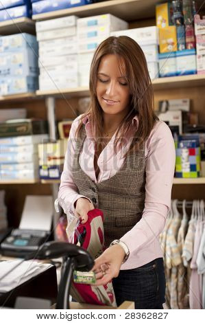 Young beautiful shop assistant at cash