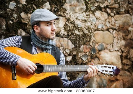 Young spanish man playing classic guitar