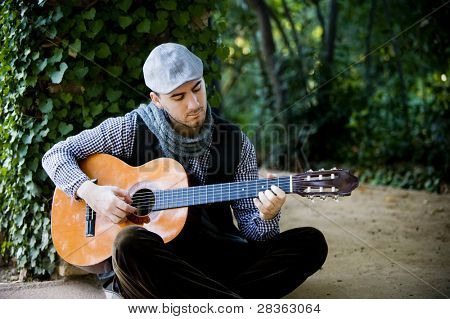 Young handsome man playing spanish guitar in green garden