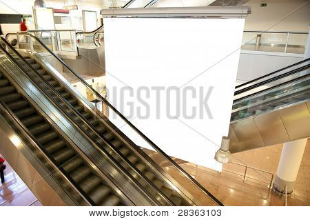Modern moving escalator in airport with empty board