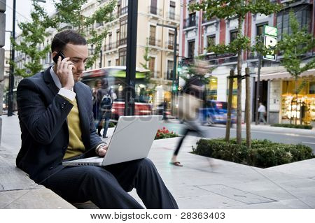 Businessman portrait with laptop and mobile phone in blurred urban background