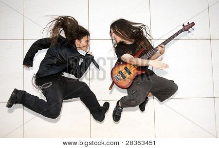 Two young musician jumping against white wall