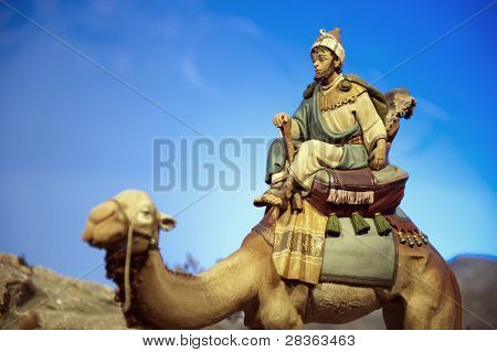 Older wise king with dromedary against blue sky.