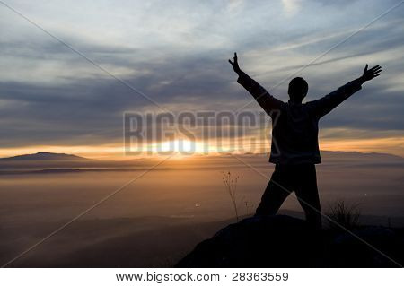 Raised arms man against beautiful sunset.