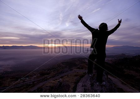 Raised arms man in the summit of mountain against beautiful sunset
