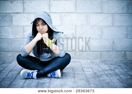 Young asian girl sitting in urban background with sad face