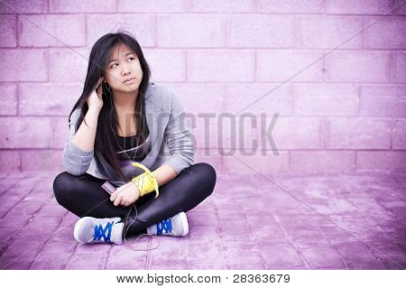 Young asian girl listening music in pink colors photo.