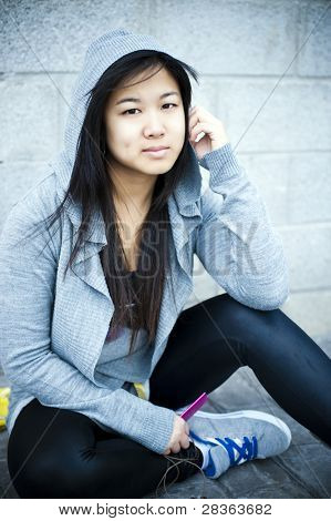 Young asian girl listening music.