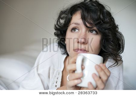 Worried brunette woman having a tea cup in bed