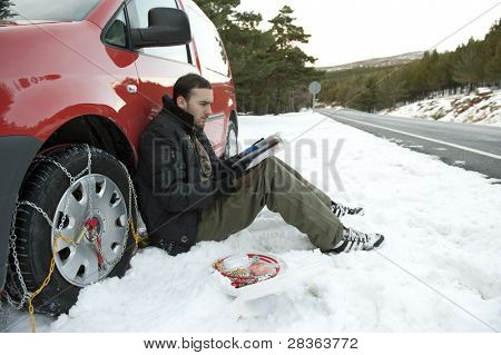 Young man reading instructions to install snow chains on his car.