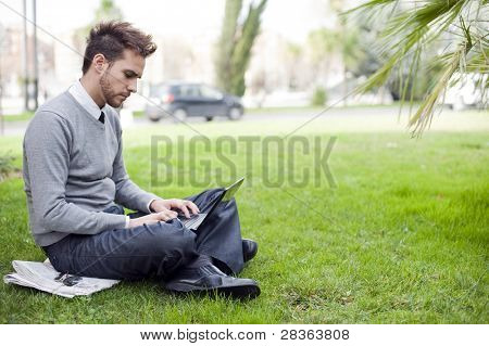 Businessman portrait using laptop in park