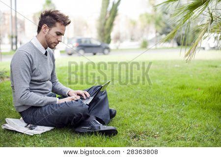 Businessman portrait using laptop in park