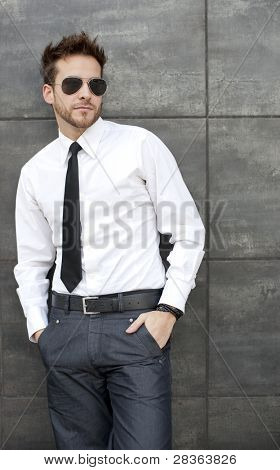 Young handsome man standing against wall with sun glasses and necktie