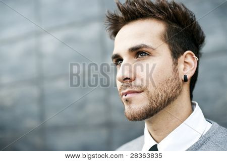 Young handsome man close portrait (piercing in ear and lips)