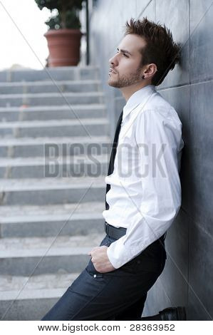 Young handsome man against wall (piercing in lips)