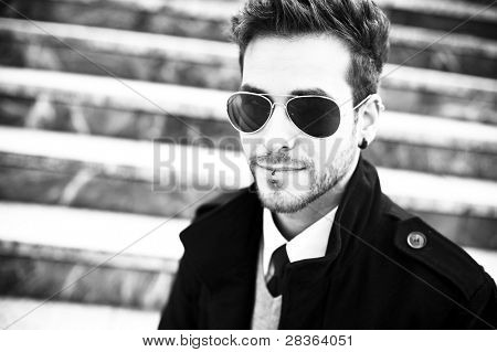 Handsome man with sunglasses staring at camera (piercing in lips and ear)