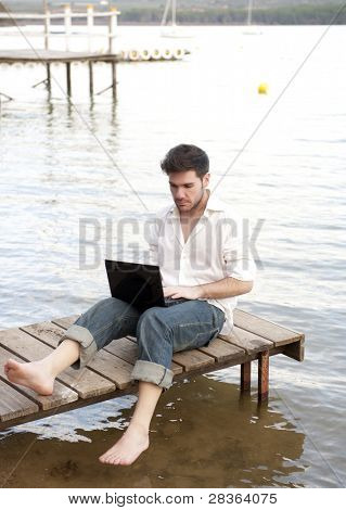 Young business man working with laptop in holidays.