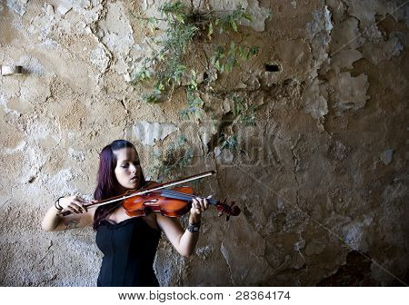 Young beautiful woman playing violin against rusty wall.