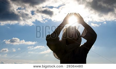Young woman doing meditation with sun in her hands.