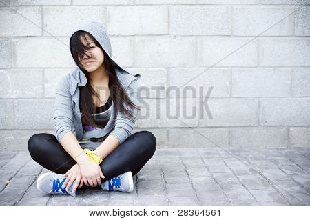 Young asian girl sitting in urban background