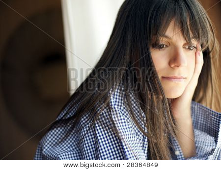 Young thoughtful woman looking outside