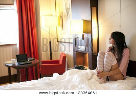 Young depressed woman in luxury bedroom