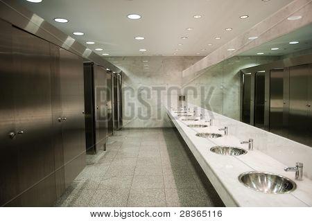 Baño público vacío con espejo de lavabos