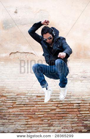 Jovem atraente dançando no fundo urbano