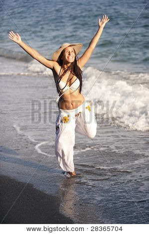 Young tanned girl with raised arms at the beach