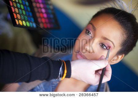 Makeup artist applying makeup to a model at a photo shoot.