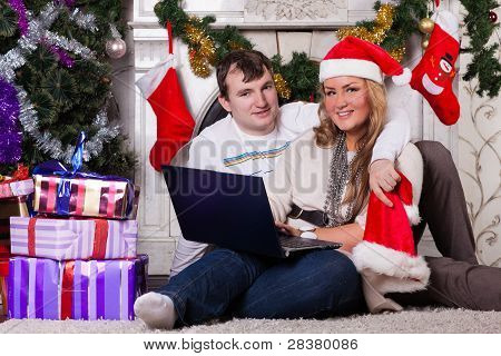 Family With Notebook Near Christmas Tree.