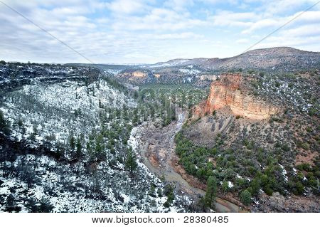 A beautiful high desert canyon with a flowing river, pine trees and snow.