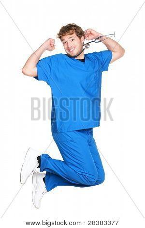 happy male nurse or doctor jumping in blue scrubs smiling excited. Young medical professional. Caucasian man in his twenties wearing stethoscope isolated on white background.