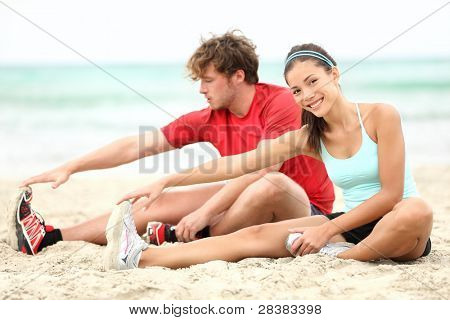 Couple training on beach stretching legs after running. Young man and woman during summer workout. Asian female fitness model, Caucasian male fitness model.