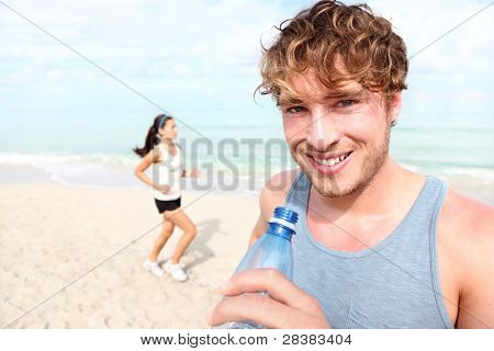 Running couple. Man drinking water smiling happy, woman runner in background. Young male fitness model in his 20s outdoors on beach
