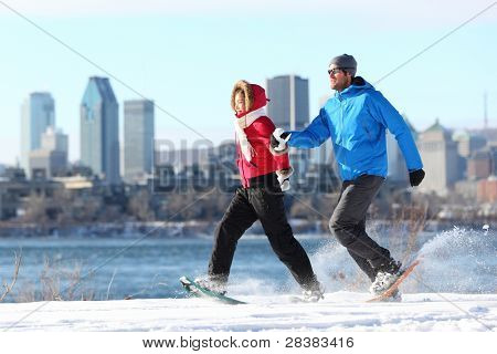 Happy couple snowshoeing running in montreal with cityscape skyline and river st. Lawrence in background. Healthy lifestyle photo from Montreal, Quebec, Canada.
