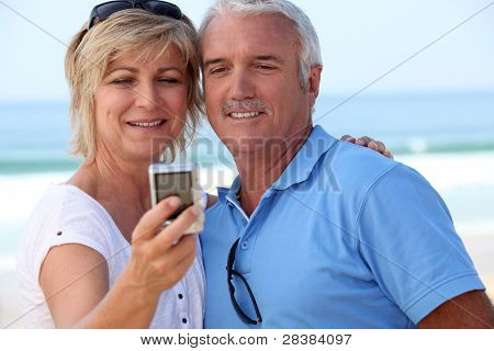 Mature couple taking a picture of themselves by the sea