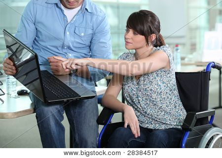 Young woman in wheelchair looking at laptop computer