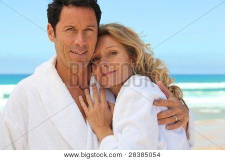 mid aged couple wearing a bathrobe near the sea
